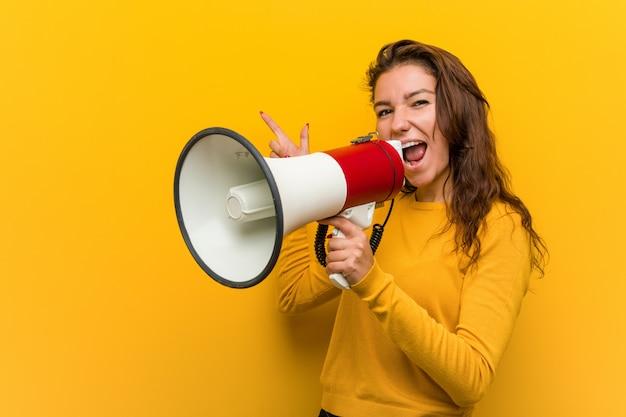 Mujer europea joven que sostiene un megáfono que sonríe alegremente que señala con el índice lejos.