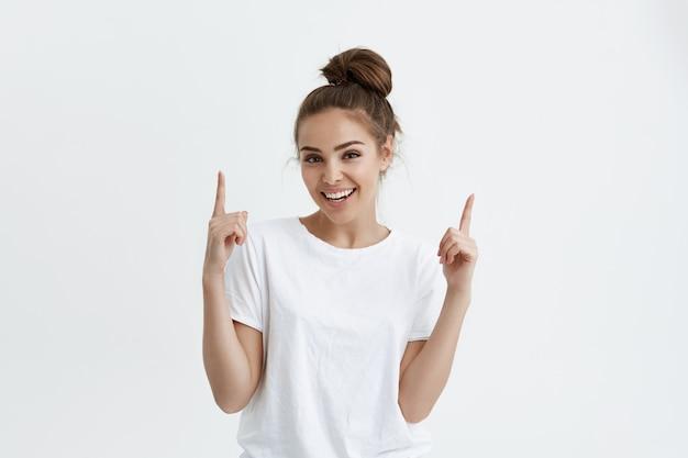 Mujer europea positiva apuntando hacia arriba con ambos dedos índices mientras sonríe alegremente