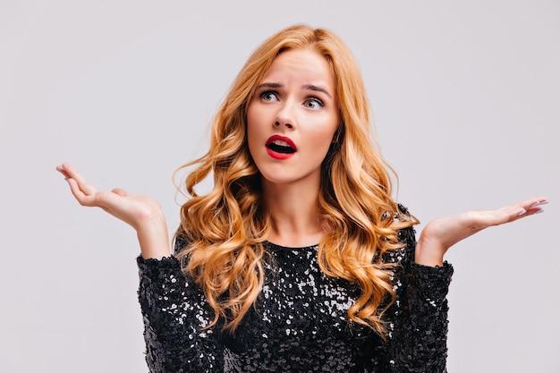 Mujer europea preocupada en vestido de fiesta agitando las manos. chica caucásica posando emocionalmente en la pared blanca.
