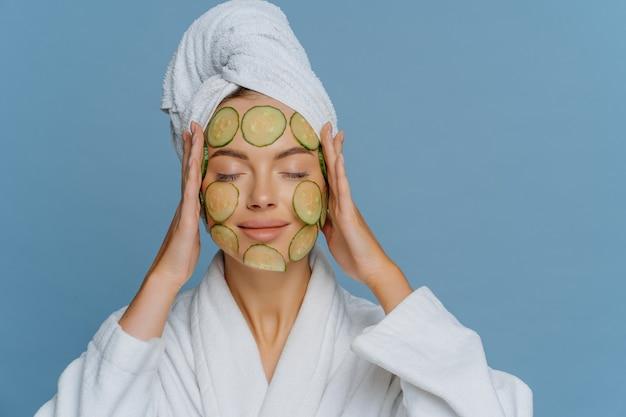 Mujer europea relajada se somete a tratamientos de belleza utiliza cosmetología natural mantiene los ojos cerrados