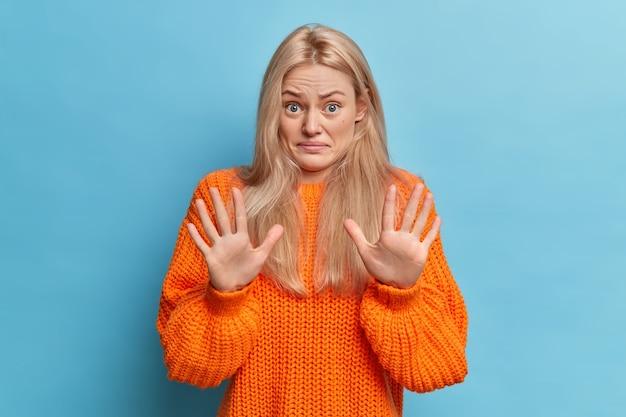 Mujer europea rubia disgustada levanta las palmas de las manos en señal de rechazo y detenga el gesto rechaza la oferta repugnante sonríe cara vestida con un jersey de punto naranja