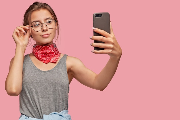 Mujer europea satisfecha toma imágenes en un teléfono celular moderno, comparte en blog