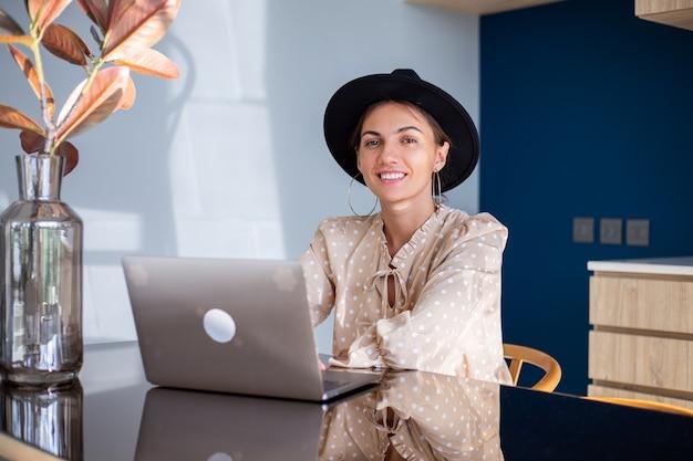Mujer europea en vestido y sombrero clásico trabaja en casa en la cocina