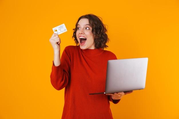 Mujer europea vistiendo un suéter con un portátil plateado y una tarjeta de crédito mientras se encuentra aislado en amarillo