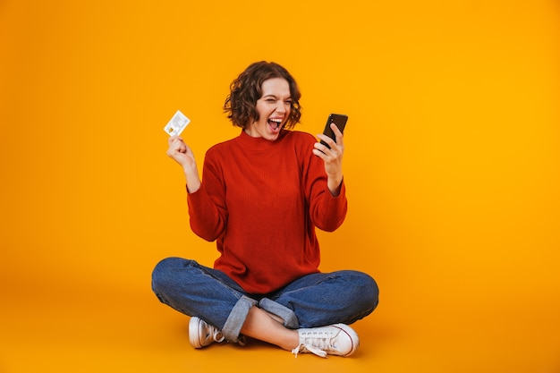 Mujer europea vistiendo un suéter con teléfono celular y tarjeta de crédito mientras está sentado en el piso aislado en amarillo