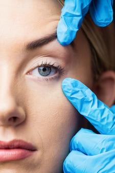 La mujer se examina la piel antes de la inyección de botox