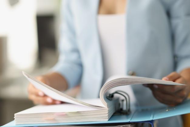 Mujer examinando información en carpeta con documentos closeup