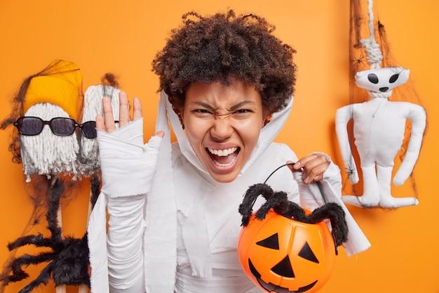 Mujer exclama en voz alta sostiene calabaza tallada con araña vestida como momia para posturas de fiesta de halloween en naranja sobre decoraciones tradicionales cuenta historias de miedo