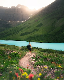 Mujer excursionista con una mochila caminando por un camino estrecho en un hermoso campo verde junto a un río