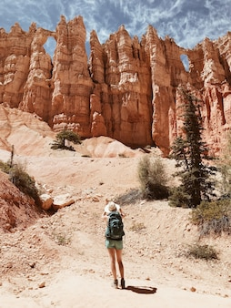 Mujer excursionista en pantalones cortos y un sombrero para el sol de pie delante de grandes formaciones rocosas y acantilados