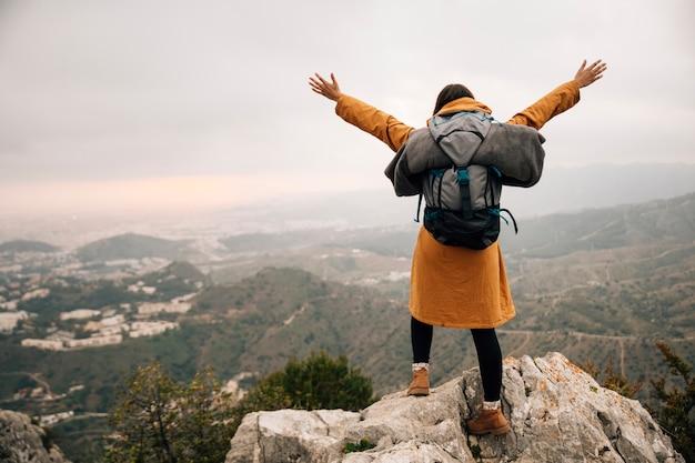 Mujer excursionista con su mochila brazos abiertos en el pico de la montaña