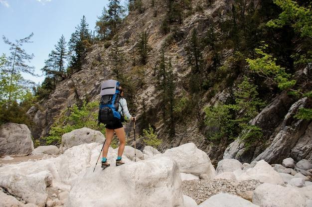 Mujer excursionista viaja a través de piedras en el cañón