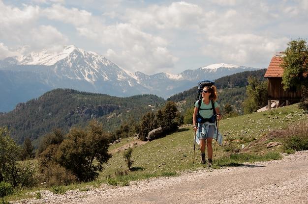 Mujer excursionista viajando cerca de la carretera en colinas