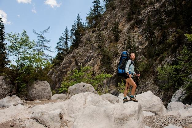 Mujer excursionista viajando a través de piedras en el cañón