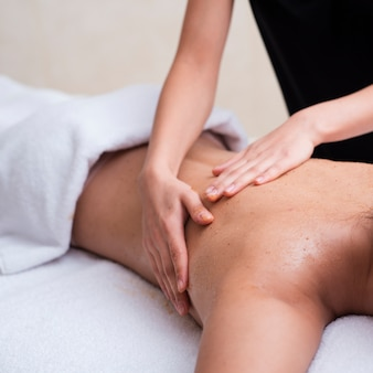 Mujer exfoliando su espalda en el spa