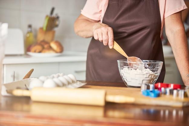 Mujer experimentada haciendo masa para pasteles caseros