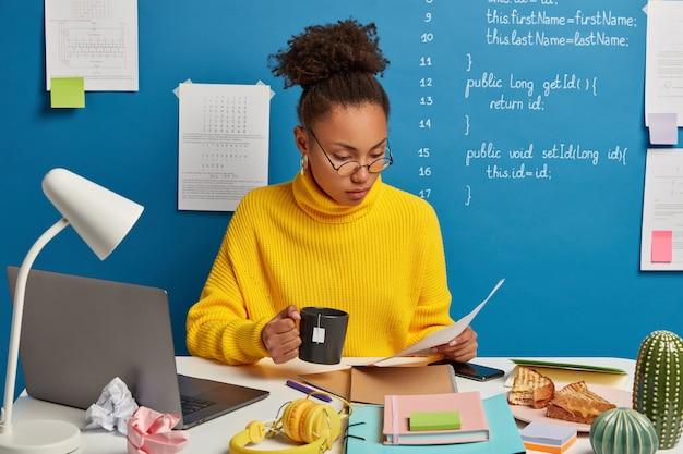 Mujer experta financiera concentrada en el contrato, examina los documentos con atención, analiza la estrategia corporativa, bebe té caliente, se sienta en el escritorio