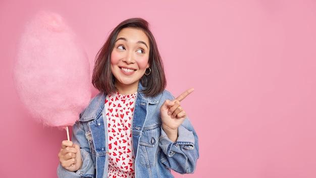 Mujer con expresión alegre sonríe agradablemente indica distancia en el espacio de copia muestra la dirección sostiene un delicioso algodón de azúcar viste una chaqueta de mezclilla