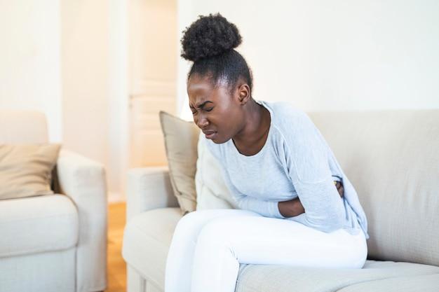 Mujer en expresión dolorosa tomados de la mano contra el vientre que sufre dolor del período menstrual, acostado triste en la cama de su casa