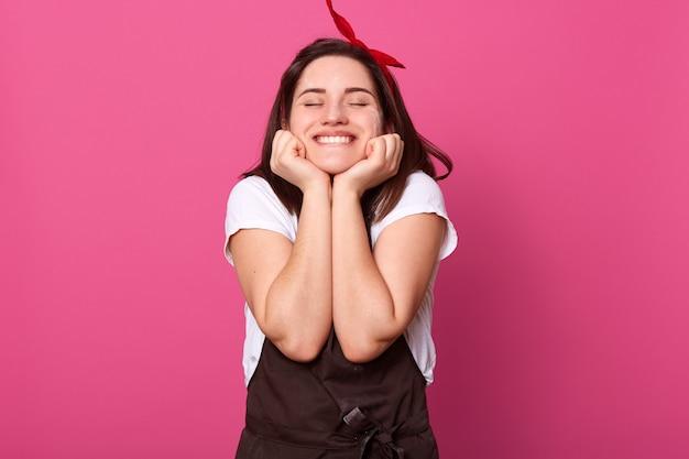 Mujer con expresión facial agradable, poniendo las manos en la cara, cerrando los ojos, sonriendo sinceramente