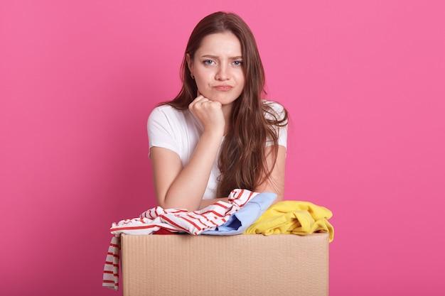 Mujer con expresión facial pensativa, posando junto a la caja con ropa vieja, decide a quién regalar cosas para uso secundario, de pie sobre rosa. concepto de donación.