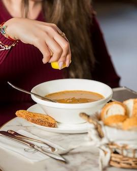 Mujer exprimiendo jugo de limón en sopa de lentejas en el restaurante