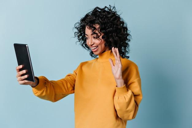 Mujer extática agitando la mano durante la videollamada