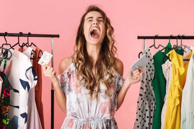 Mujer extática de pie cerca del armario mientras sostiene el teléfono inteligente y la tarjeta de crédito aislado en rosa