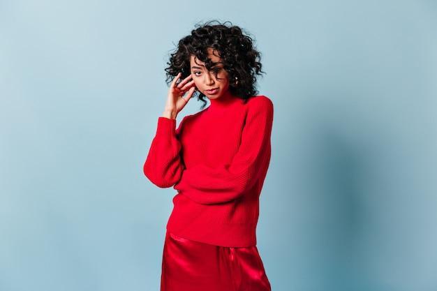 Mujer extática en traje rojo mirando al frente