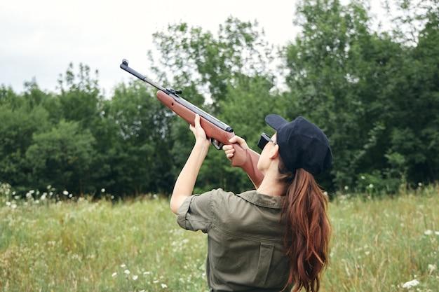 Mujer en el exterior sosteniendo una pistola a la vista la caza de hojas verdes vista recortada
