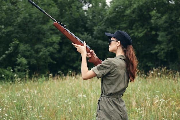 Mujer en el exterior sostiene la pistola apuntando a la caza verde vista recortada