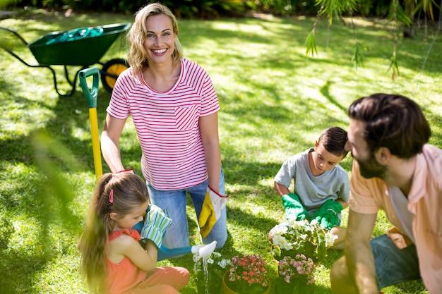 Mujer con familia durante la jardinería en el patio