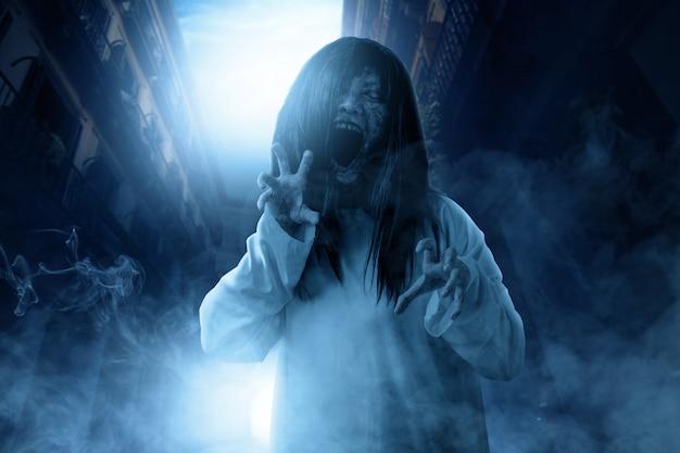 La mujer fantasma aterradora con sangre y cara enojada con manos arañando frecuentaba el edificio abandonado
