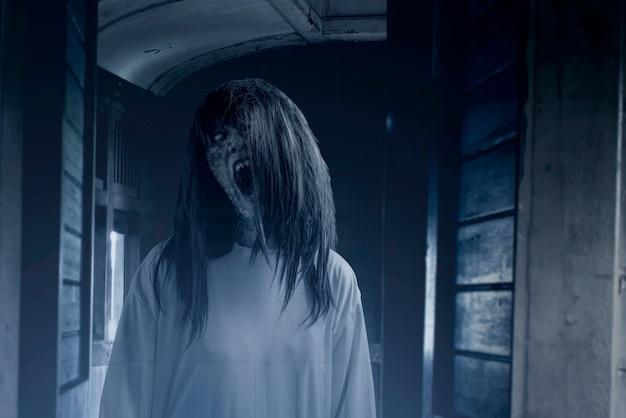 Mujer fantasma aterradora con sangre y cara enojada en el viejo vagón