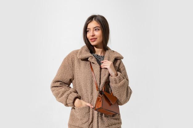 Mujer fascinante en abrigo de piel de invierno posando.