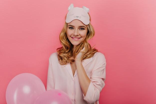 Mujer fascinante con peinado ondulado esperando regalos en su cumpleaños. foto interior de niña rubia en máscara de dormir sosteniendo globos de helio.