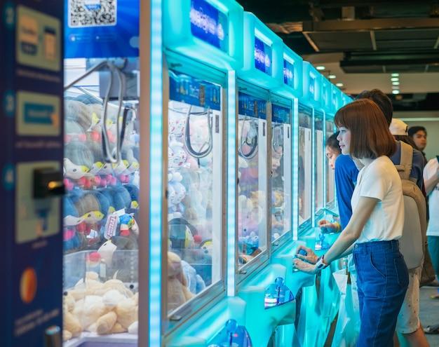 Mujer de felicidad jugando juego de garra o gabinete para atrapar a las muñecas
