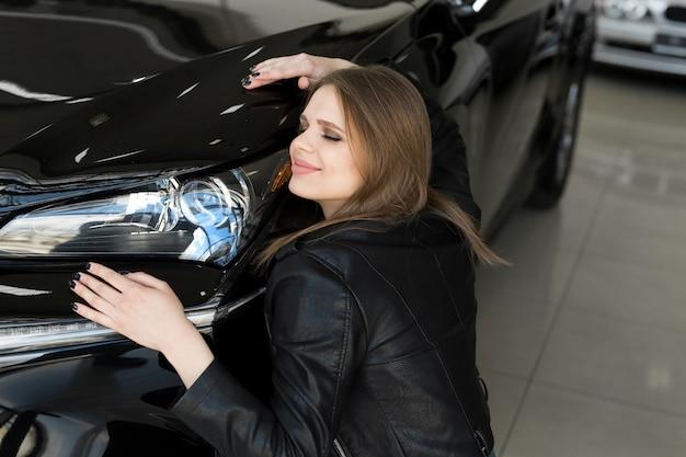 Mujer feliz abraza el capó de su coche nuevo