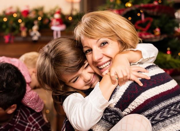 Mujer feliz abrazando a su hija pequeña en navidad