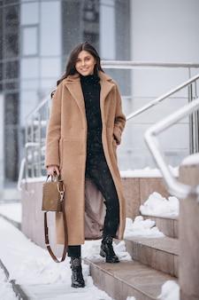 Mujer feliz en abrigo en invierno afuera