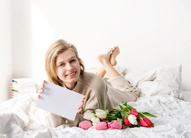 Mujer feliz acostada en la cama en pijama, sosteniendo un ramo de flores de tulipán y una tarjeta en blanco para un diseño de maqueta