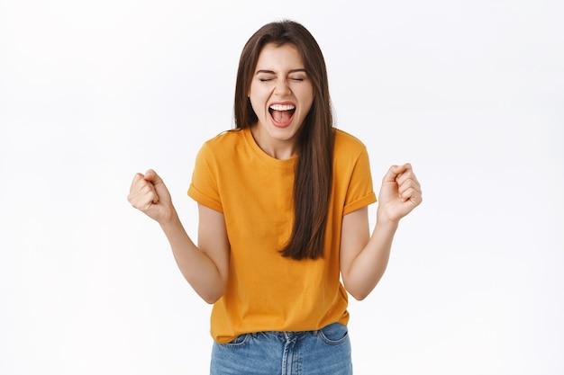 Mujer feliz y aliviada que se regocija con una camiseta amarilla, aprieta los puños y sonríe con alegría, logra el éxito, tiene la suerte de ganar el premio, se convierte en campeona, cierra los ojos y grita satisfecho, triunfando