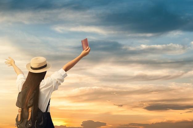 Mujer feliz aparece pasaporte con puesta de sol.