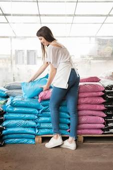 Mujer feliz apilando sacos de plástico en invernadero