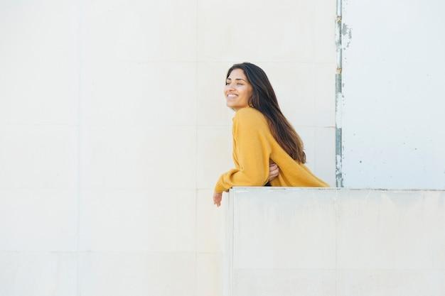 Mujer feliz apoyado en el balcón mirando afuera
