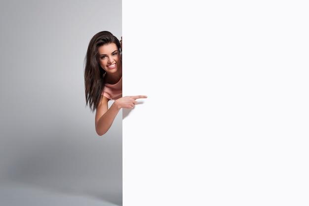 Mujer feliz apuntando al espacio de la copia en la pizarra