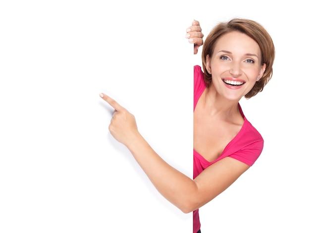 Mujer feliz apuntando con su dedo en banner aislado en la pared blanca