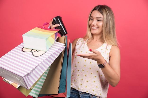 Mujer feliz apuntando sus bolsas de la compra y una taza de café.