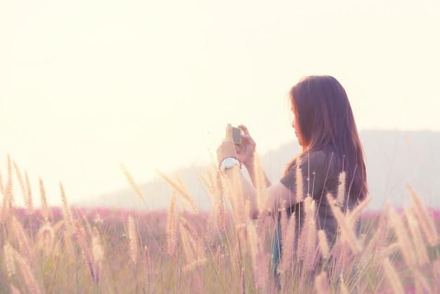 La mujer feliz asiática del pelo largo utiliza el teléfono móvil elegante toma la foto de la visión que se coloca en campo del cosmos en estilo de la imagen del vintage.