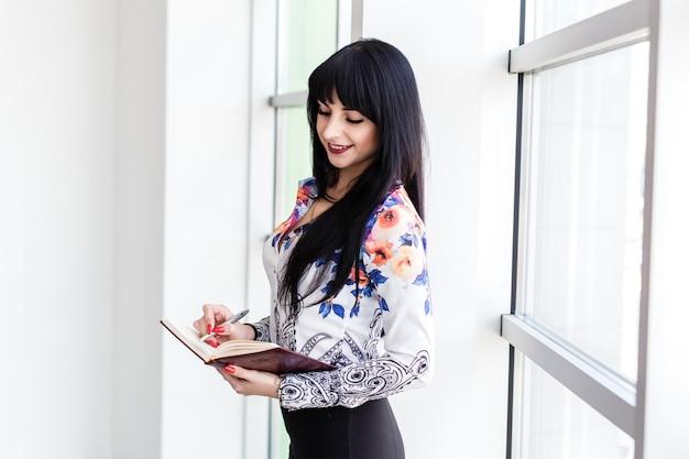 Mujer feliz atractiva joven que se coloca cerca de la ventana, escribiendo en un cuaderno, mirando al cuaderno, sonriendo.